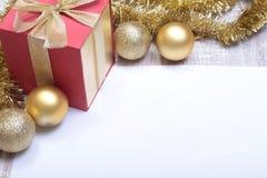 Mandi un sms al Buon Natale su carta con le palle ed il contenitore di regalo Fotografia Stock