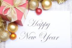 Mandi un sms al Buon Natale su carta con le palle ed il contenitore di regalo Immagine Stock