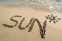 Mandi un sms al profilo del sole sulla spiaggia sabbiosa bagnata Fotografia Stock