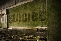 Mandi un sms al suicidio sulla parete sporca in una casa rovinata abbandonata fotografia stock