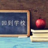 Mandi un sms a di nuovo alla scuola scritta in cinese su una lavagna Fotografie Stock Libere da Diritti