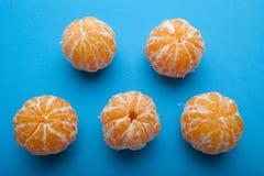 Mandirins anaranjados sin la cáscara en un fondo azul foto de archivo