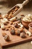 Mandlar, kasjujordnöt, hasselnötter i träbunkar på trä och säckväv, säckbakgrund Fotografering för Bildbyråer