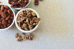 Mandlar pecannötter, valnötter i behållare, placerade av övreLef Arkivfoto