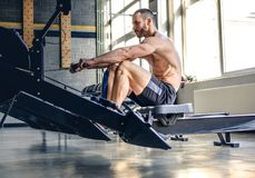 A mandoing workouts on a back with power exercise machine. Athletic shirtless male doing workouts on a back with power exercise machine in a gym club Royalty Free Stock Photography
