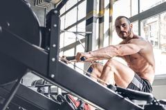 A mandoing workouts on a back with power exercise machine. Athletic shirtless male doing workouts on a back with power exercise machine in a gym club Stock Photography