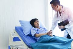 Mandoktorn som kontrollerar tryck av den kvinnliga patienten, ?ldre sjuk kvinnapatient, l?gger p? s?ng i sjukhus med intraven?s n arkivbilder
