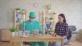 Mandoktorn tar salivanalys från munnen av en ung kvinna med en bomullsbomullstopp stock video
