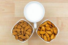 Mandorla sgusciata secca ed inzuppata con la tazza del latte della mandorla su woode Fotografia Stock