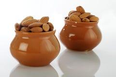 Mandorle asciutte di frutti in vaso ceramico su bianco Fotografia Stock