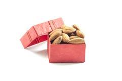mandorle, gruppo della mandorla, mandorle in contenitore di regalo rosso sopra sopra la parte posteriore di bianco Fotografie Stock