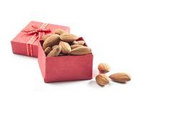 mandorle, gruppo della mandorla, mandorle in contenitore di regalo rosso sopra sopra la parte posteriore di bianco Fotografia Stock Libera da Diritti