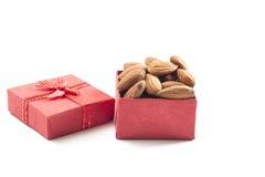 mandorle, gruppo della mandorla, mandorle in contenitore di regalo rosso sopra sopra la parte posteriore di bianco Immagini Stock