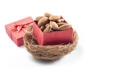 mandorle, gruppo della mandorla, mandorle in contenitore di regalo rosso sopra sopra la parte posteriore di bianco Fotografie Stock Libere da Diritti