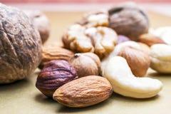 Mandorle, nocciole, anacardi ed intere noci su fondo dorato Spuntino organico sano, prima colazione, ingredienti alimentari fotografia stock libera da diritti