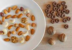 Mandorle, nocciole, noci, anacardi su un piatto bianco, tre intere noci, interi cereali croccanti del grano intorno all'avena su  fotografia stock