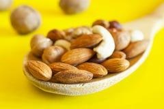 Mandorle, nocciole, noci, anacardi in un cucchiaio di legno e tre intere noci isolate su fondo giallo Organico sano immagini stock