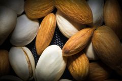 Mandorle, pistacchi, anacardii misti insieme su fondo nero fotografie stock