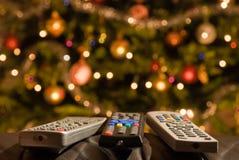 Mandos a distancia delante del árbol de navidad encendido Fotos de archivo libres de regalías