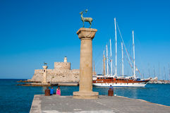 Mandraki港口和古铜鹿雕象,希腊 免版税库存照片