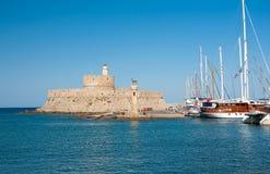 Mandraki港口和老灯塔。 库存照片