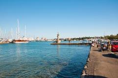 Mandraki港口和老灯塔。 免版税库存图片