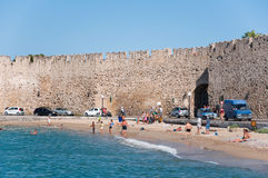 Mandraki hamn och en strand, Rhodes, Grekland. Arkivfoton