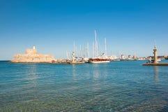 Mandraki harbor and the old lighthouse. Stock Photos