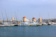 The Mandraki harbor in Rhodes town, Greece. Stock Images