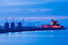 Mandraki Harbour Rhodes. Night shot of the windmills and lighthouse at Mandraki harbour Rhodes Greece stock photo