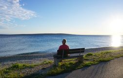 Mandre, Island of Pag, Croatia, Jun 22, 2018. Old man sitting on the bench by the sea and looking in the distance at sunset stock photos