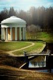 Mandril clássico branco com colunas em um parque bonito com trajetos e uma ponte através de um córrego, vertical Imagem de Stock Royalty Free