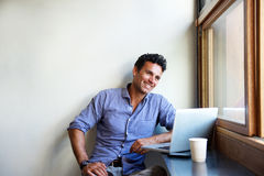 Mandsome modern man smiling with laptop at cafe Royalty Free Stock Photo