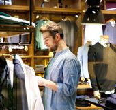 Mandsome young man shopping for clothes at shop. Portrait of a handsome young man shopping for clothes at shop Royalty Free Stock Photo