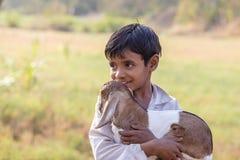 Indian boy on the street with goatling. Mandu, India