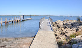 Mandurah Boat Docks in Western Australia. Wooden boat docks in diminishing perspective near rocky edge in Mandurah, Western Australia with boats on the water royalty free stock photo