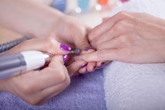 Manecurist perfoming finger nail procedure for hand care in beau Stock Photos