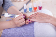 Manecurist perfoming finger nail procedure for hand care in beau Royalty Free Stock Image