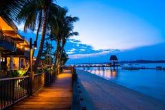 Maneira de madeira da caminhada na praia na noite com luz morna Fotos de Stock Royalty Free