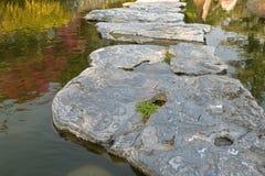 Maneira natural enorme do trajeto da pedra da etapa de andar no jardim da lagoa de água em Fotos de Stock Royalty Free