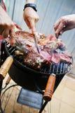 Manejando y cortando la carne de la barbacoa Imágenes de archivo libres de regalías