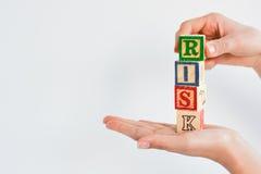 Maneje el concepto del riesgo de negocio con la mano humana y los bloques de madera Imagen de archivo libre de regalías