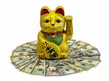 Gilded Chinese Asian or Feng Shui lucky charm cat with a paw raised in greeting denoting wealth and prosperity over a white backgr. The Maneki- Neki Cat is royalty free stock photography