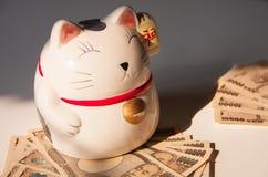Maneki-neko,与日元钞票的日本幸运的猫 免版税图库摄影