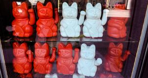 Maneki neko also known as chinese fortune cat. Showcase with welcoming souvenir cats beckoning to enter stock photos