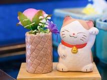 Maneki Neko cat in the coffee shop. Maneki Neko in the coffee shop Royalty Free Stock Photos