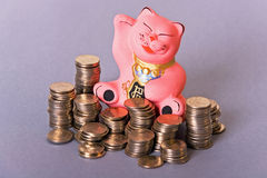 Maneki neko cat with coins. Maneki neko pink cat among columns of coins Royalty Free Stock Photo
