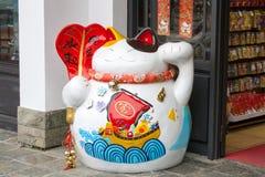 Maneki Neko cat. Common Japanese sculpture bring Stock Photography
