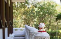 Maneki Neko ceramics figurine. Japanese lucky charm talism: Maneki Neko. Brings good fortune and money according do tradition. Background of bamboo forest Royalty Free Stock Images