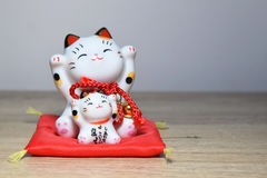 Maneki-neko is a common Japanese figurine beckoning cat. Stock Photos